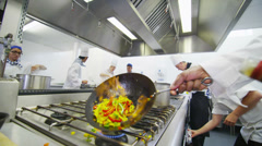 Professional chef in a commercial kitchen cooking flambe style Stock Footage