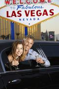 Couple In Limousine With Champagne Flutes By Welcome To Las Vegas Sign Stock Photos