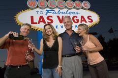 Friends With Champagne Against 'Welcome To Las Vegas' Sign - stock photo