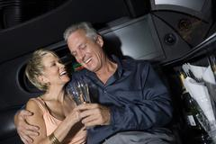 Couple With Champagne Sitting In Limousine - stock photo