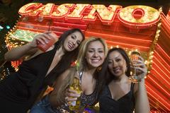 Stock Photo of Women Holding Champagne With Casino In The Background