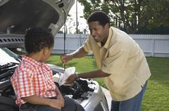 Boy Looking At Father Checking Engine Oil Stock Photos