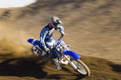Motocross Racer Riding Motorcycle On Dirt Track - stock photo