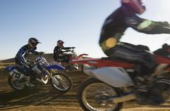 Motocross Racers Racing In Desert - stock photo