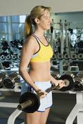 Woman Exercising With Barbell In Gym Stock Photos