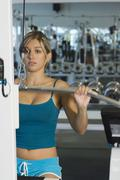 Woman Lifting Weights On A Lat Pull Machine Stock Photos