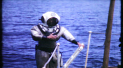 16 - deep sea diver gets assistance with gear - vintage film home movie Stock Footage