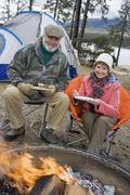 Senior Couple Having Food At Campfire - stock photo