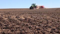 Agriculture tractor with machine sowing seeds and cultivating field in autumn Stock Footage