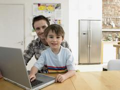 Son And Father With Laptop Sitting At Table - stock photo