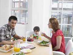 Parents And Son Having Meal At Dining Table Stock Photos