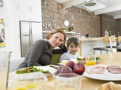 Happy Mother And Son Having Meal At Dining Table Stock Photos