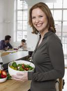 Stock Photo of Mother Holding Bowl Of Salad With Family Sitting In Background
