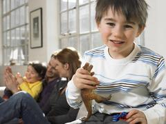 Boy Holding Animal Toy With Family Smiling In Background Stock Photos