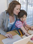 Mother Using Laptop While Daughter Coloring Book At Table Stock Photos
