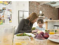 Son And Mother Having Meal At Dining Table In Kitchen Stock Photos
