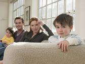 Stock Photo of Cute Boy With Family Sitting On Sofa