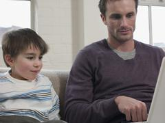 Boy And Father Looking At Laptop In House - stock photo