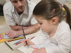 Girl Coloring Pictures With Father Looking At It Stock Photos
