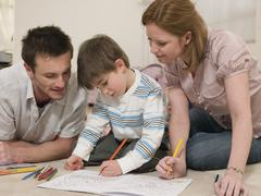 Parents Looking At Son Coloring In Drawing Book Stock Photos