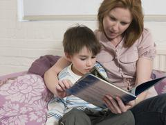 Woman And Son With Picture Book Looking At Each Other - stock photo