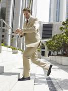 Businessman Climbing Office Steps While Looking At Wristwatch - stock photo
