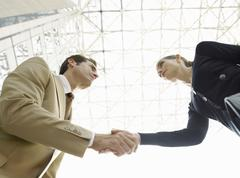Confident Businesspeople Shaking Hands Against Ceiling - stock photo