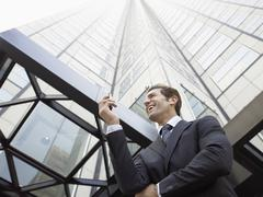 Stock Photo of Businessman Reading SMS On Mobile Phone Against Office Building