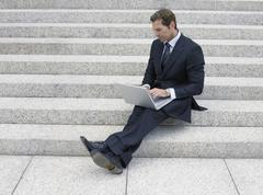 Stock Photo of Businessman Using Laptop Of Office Steps