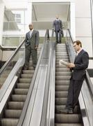Multi Ethnic Businessmen Standing On Escalator In Office - stock photo