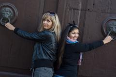 Two women knocking on the door with knockers Stock Photos