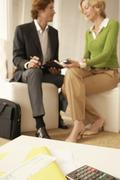 Calculator And Documents On Table With Businesspeople In Office Lobby Stock Photos