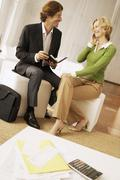 Businesswoman Using Mobile Phone While Looking At Businessman In Lobby - stock photo