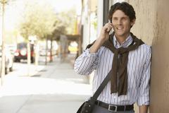 Businessman Using Mobile Phone While Leaning On Wall - stock photo