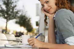 Young Businesswoman Writing On Paper At Outdoor Cafe - stock photo