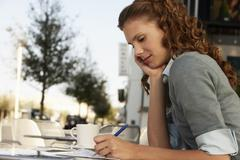 Stock Photo of Businesswoman Writing On Paper At Outdoor Cafe