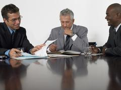 Stock Photo of Businessmen Reading Documents In Conference Room
