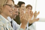 Stock Photo of Business People Applauding At Conference Table