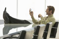 Relaxed Businessman Text Messaging On Cell Phone In Conference Room Stock Photos