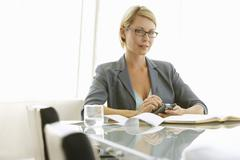 Businesswoman Using Mobile Phone At Conference Table Stock Photos