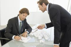 Angry Businessman With Male Colleague Writing On Paper Stock Photos