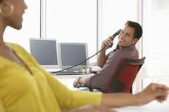 Businessman Using Landline Phone In Office - stock photo