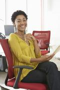 Happy Woman With Pencil And Notepad Sitting On Office Chair - stock photo