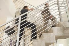 Businessmen Moving Upstairs In Office - stock photo