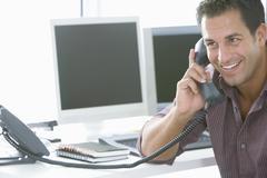 Happy Businessman Using Landline Phone In Office - stock photo
