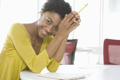 Businesswoman With Notepad And Pencil Sitting At Table Stock Photos