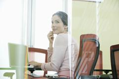 Stock Photo of Businesswoman Using Laptop In Conference Room