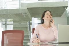 Businesswoman Using Mobile Phone While Writing On Notepad - stock photo