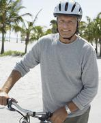 Stock Photo of Senior Man With Bicycle On Tropical Beach