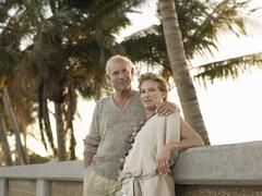 Loving Senior Couple Leaning Against Wall On Beach Stock Photos